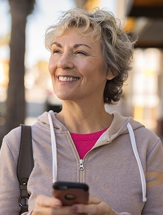 Smiling older woman outdoors holding cellphone